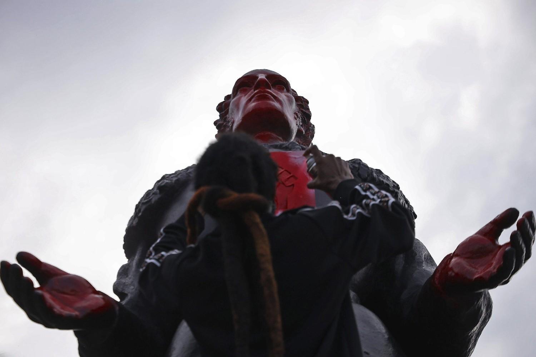 Demonstrant crvenim sprejom vandalizuje spomenik Kristoferu Kolumbu u Majamiju tokom protesta zbog ubistva Džordža Flojda (Foto: Carl Juste /Miami Herald via AP)