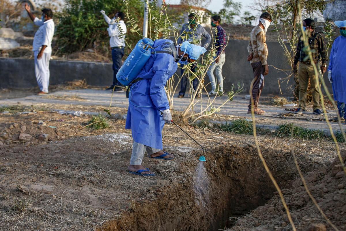 Radnik u zaštitnom odelu vrši dezinfekciju grobnih mesta na groblju u Ahmedabadu, 28. mart 2020. (Foto: PTI Photo)