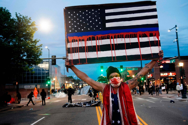 "Demonstrant drži transparent na kome američka zastava ""krvari"" tokom protesta zbog ubistva Džordža Flojda, Denver, 31. maj 2020. (Foto: Jason Connolly/AFP)"