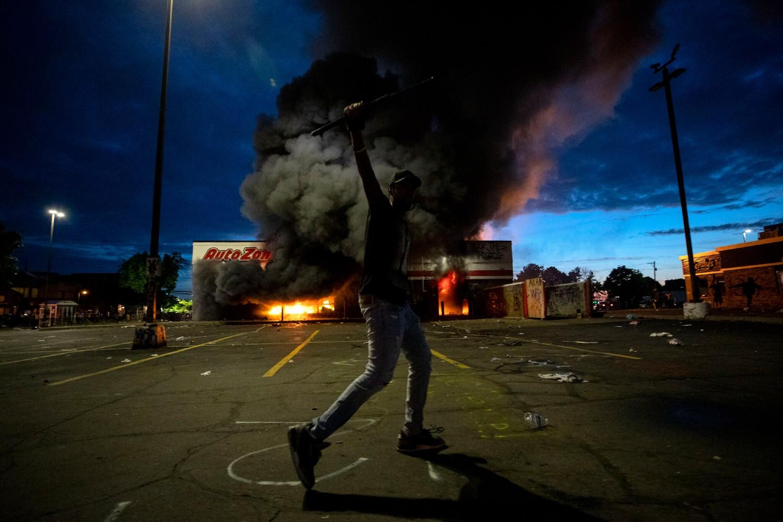 Demonstrant gestikulira rukom ispred zapaljene prodavnice za auto delove tokom protesta zbog ubistva Džordža Flojda, Mineapolis, 27. maj 2020. (Foto: Carlos Gonzalez/Star Tribune via AP)