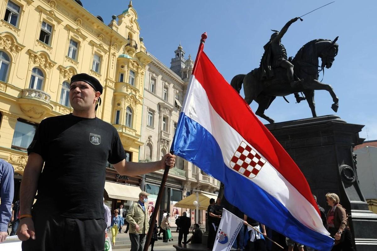 Pripadnik ustaškog pokreta drži zastavu sa ustaškim grbom u Zagrebu (Foto: Profimedia)