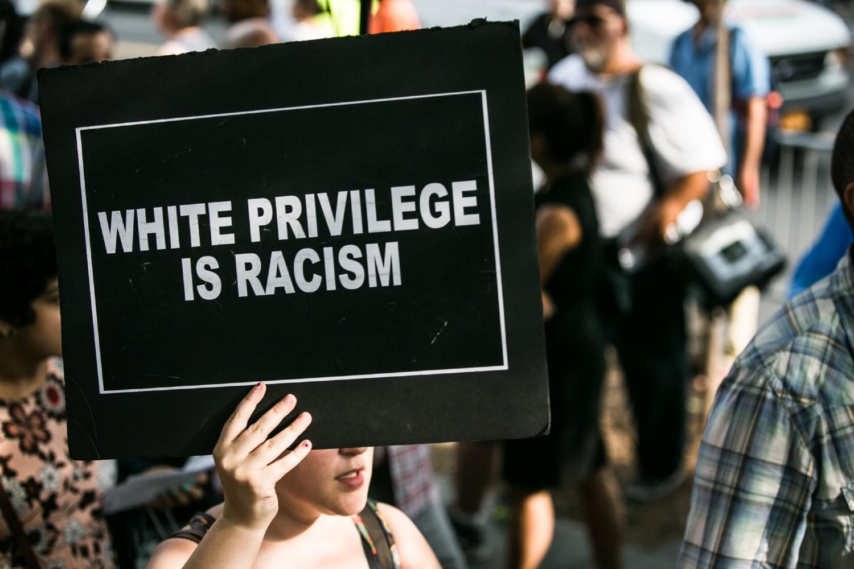 """Demonstrant sa transparentom na kome piše """"Belačka privilegovanost je rasizam"""" tokom jednog protesta u Sjedinjenim Državama 2016. godine (Foto: Karla Ann Cote/NurPhoto via Getty Images)"""