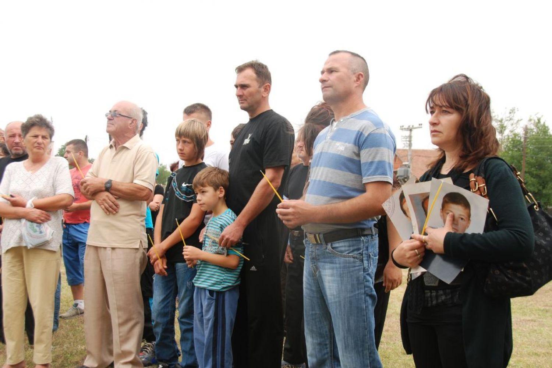 Ožalošćeni sa svećama i slikama ubijenih žetelaca tokom parastosa 2012. godine (Foto: Eparhija raško-prizrenska/spc.rs)