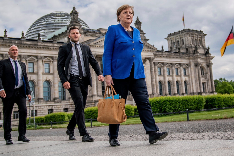 Nemačka kancelarka Angela Merkel u pratnji svojih telohranitelja prolazi pored Bundestaga, Berlin, 13. maj 2020 (Foto: AP Photo/DPA/Michael Kappeler)