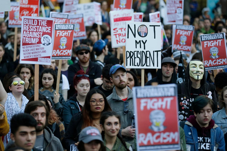 Demonstranti sa transparentima uperenim protiv Donalda Trampa na protestima povodom njegovog izbora na mesto predsednika SAD, Sijetl, 09. novembar 2016. (Foto: AP Photo/Ted S. Warren)