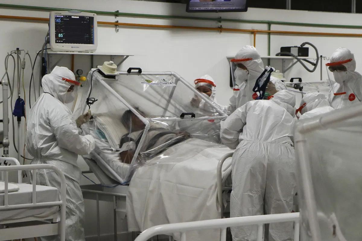 Lekari u zaštitnim odelima pomažu pacijentu obolelom od virusa COVID-19 u bolnici u Manausu, Brazil, 14. april 2020. (Foto: AP Photo/Edmar Barros)