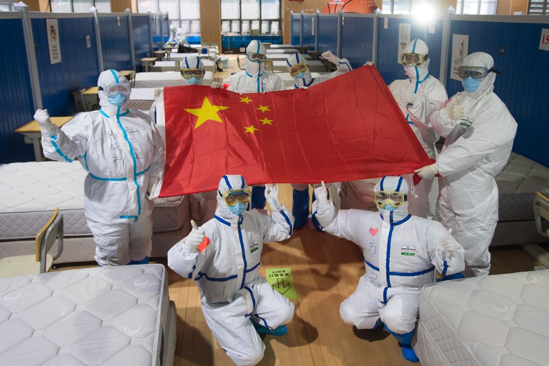 Кинески медицински радници позирају са заставом Кине након затварања привремене ковид болнице у Вухану, 10. март 2020. (Фото: Xinhua/Xiao Yijiu)