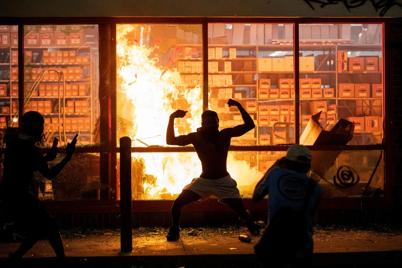 Demonstrant pozira ispred prodavnice u kojoj je podmetnut požar tokom protesta zbog ubistva Džordža Flojda, Mineapolis, 27. maj 2020. (Foto: Carlos Gonzalez/Star Tribune via AP)