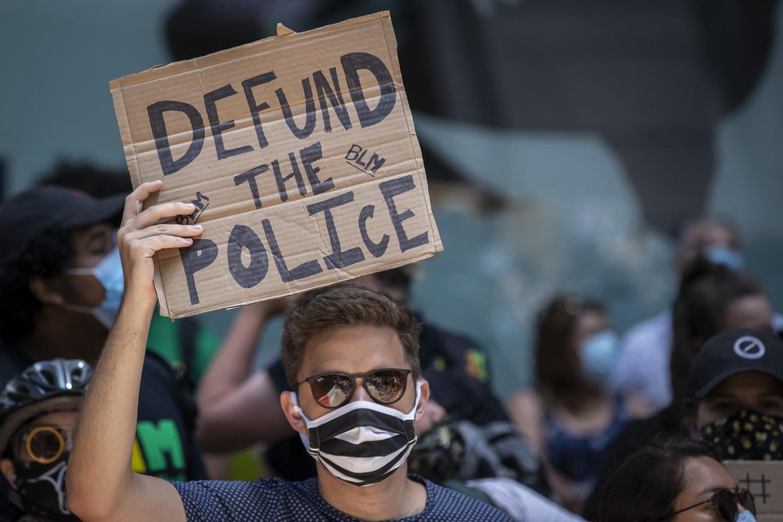 """Demonstrant drži transparent na kome piše """"Defundirajte policiju"""" tokom protesta zbog ubistva Džordža Flojda, Njujork, 07. jun 2020. (Foto: Ira L. Black/Corbis via Getty Images)"""