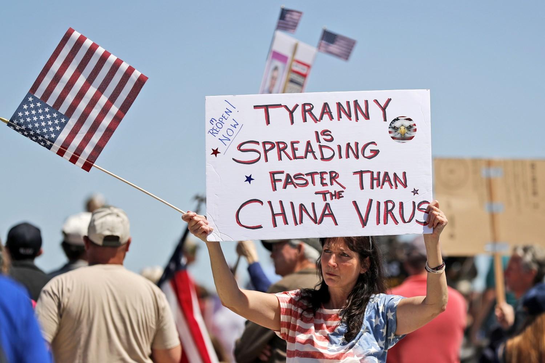 """Žena drži transparent na kome piše """"Tiranija se širi brže od kineskog virusa"""", tokom protesta zbog uvođenja karantina, Džefereson Siti (Misuri), 21. april 2020. (Foto: AP Photo/Jeff Roberson)"""