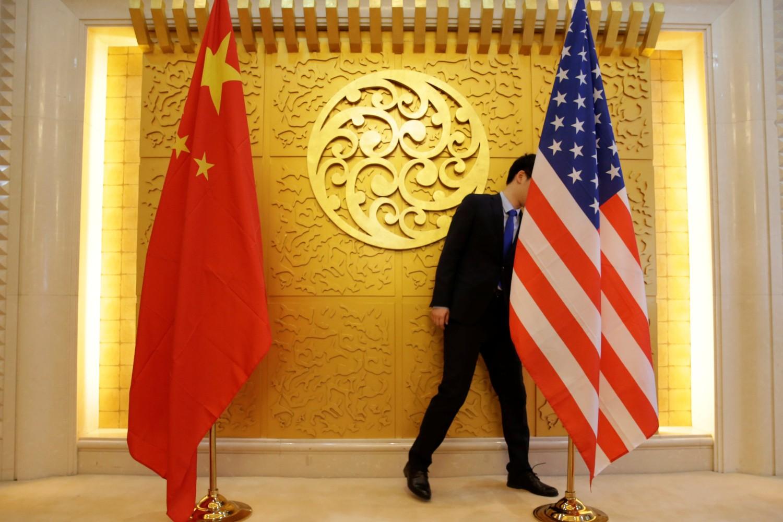 Član protokola postavlja američku i kinesku zastavu pre sastanka kineskih i američkih zvaničnika, Peking, 27. april 2018. (Foto: REUTERS/Jason Lee)