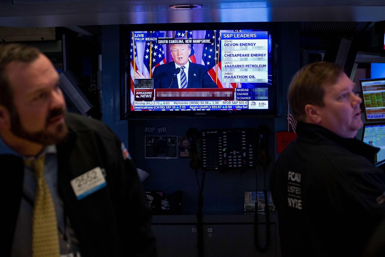 Radnici na Njujorškoj berzi posmatraju kretanja cena dok se u pozadini emituje TV prilog sa Donaldom Trampom (Foto: Michael Nagle/Bloomberg/Getty Images)