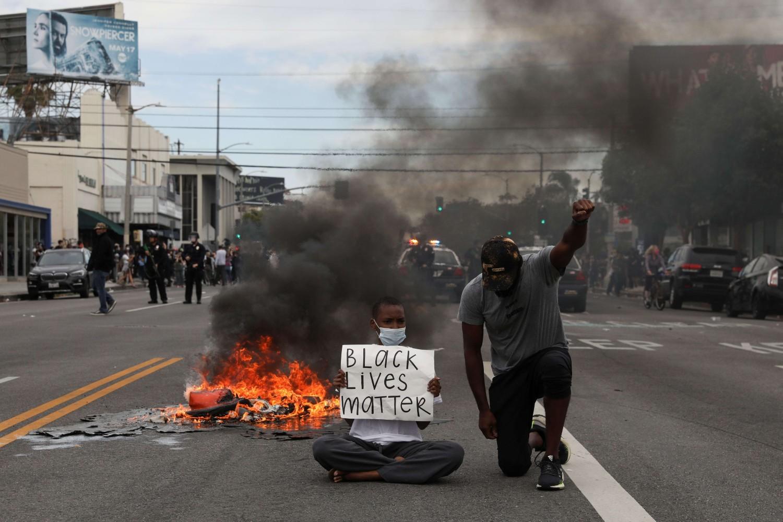 """Jedan demonstrant sedi na putu sa transparentom u rukama na kome piše """"Crni životi su važni"""", dok drugi kleči na jednom kolenu sa stisnutom pesnicom tokom protesta zbog ubistva Džordža Flojda, Los Anđeles, 30. maj 2020. (Foto: AP Photo/Mark J. Terrill)"""