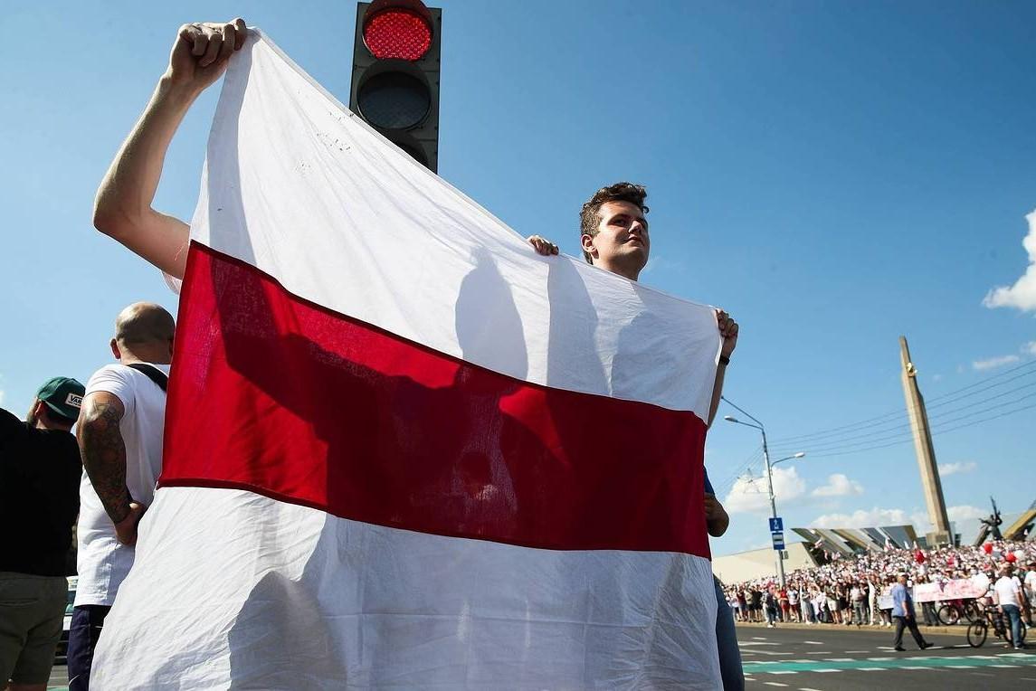 Demonstranti sa zastavom tokom protesta u Minsku zbog rezultata predsedničkih izbora u Belorusiji (Foto: Nataliя Fedosenko/TASS)