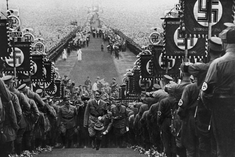 Nacistički vođa Adolf Hitler okružen vojnicima sa nacističkim zastavama tokom prolaska kroz špalir prilikom jednog mitinga na Bukebergu (Foto: Hulton Archive/Getty Images)