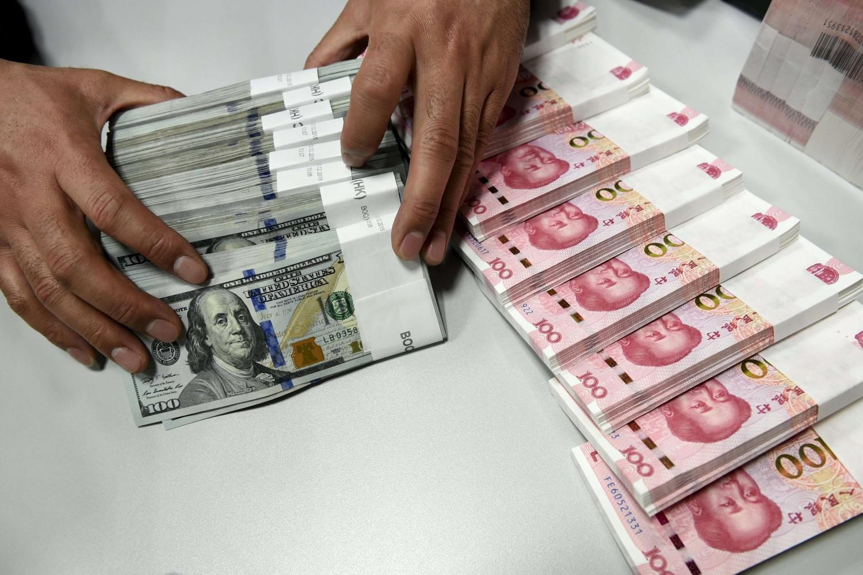 Bankarski službenik prebrojava i pakuje američke dolare i kineske juane u jednoj od filijala Banke Kine (Foto: Reuters/Jon Woo)