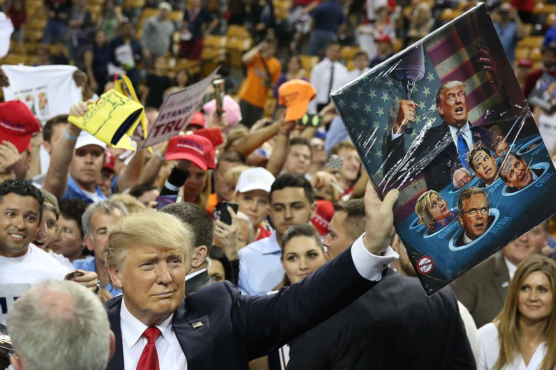 Donald Tramp okružen svojim pristalicama sa slikom na kojoj se on bori protiv svojih protivnika (Foto: Joe Raedle/Getty Images)