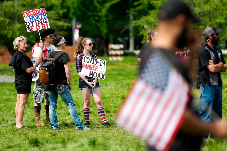Demonstranti sa američkim zastavama i plakatima tokom protesta zbog karantina prouzrokovanog širenjem epidemije virusa COVID-19, Olimpija, Vašington, 09. maj 2020. (Foto: Jason Redmond/Agence France-Presse/Getty Images)