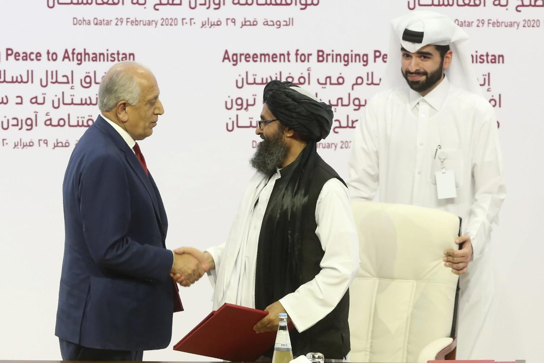 Rukovanje američkog mirovnog izaslanika za Avganistan Zalmaja Kalizada i vrhovnog političkog lidera talibana mule Abdula Ganija Baradara nakon potpisivanja mirovnog sporazuma, Doha, 29. februar 2020. (Foto: AP Photo/Hussein Sayed)