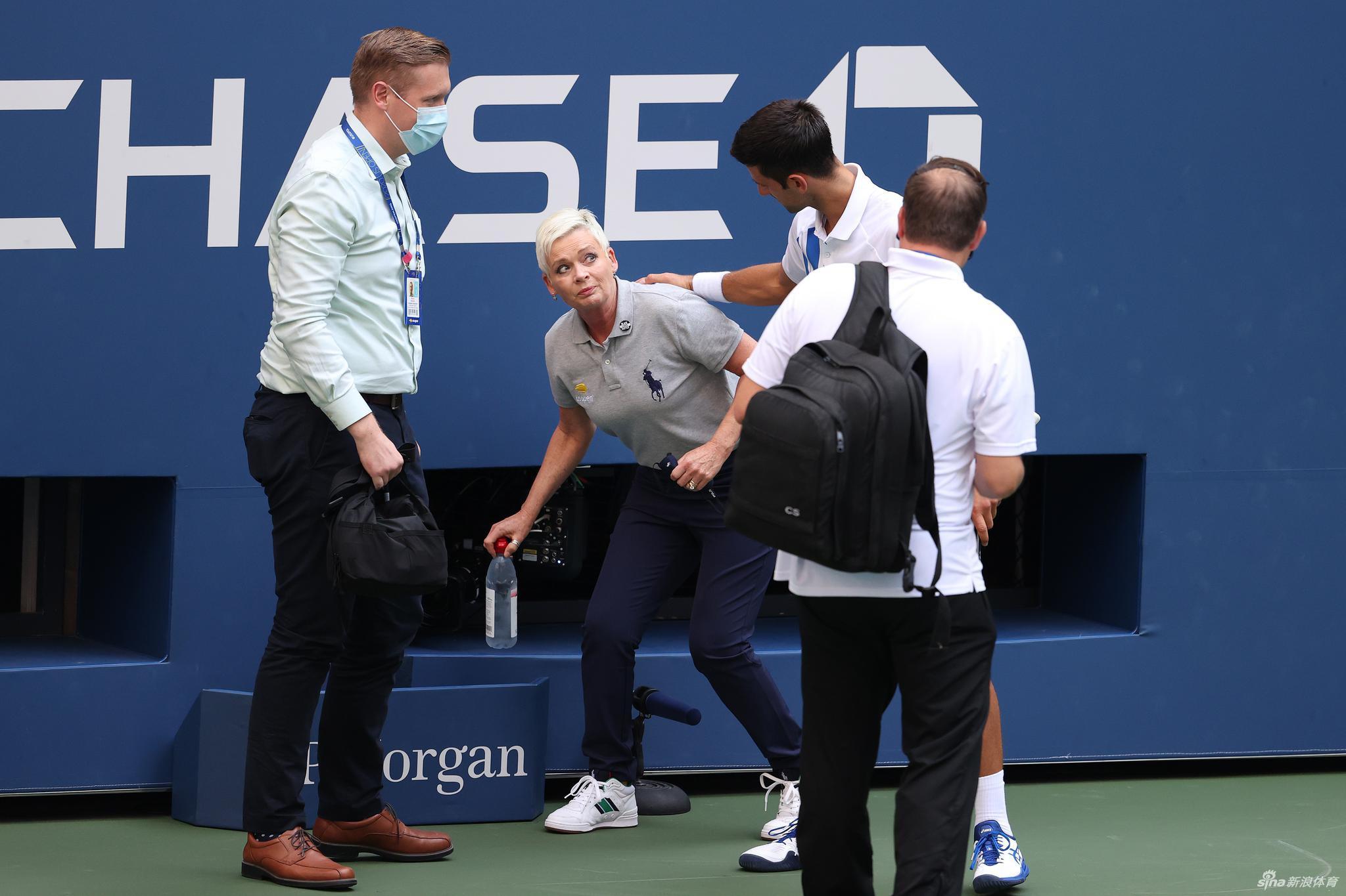 Najbolji svetski teniser Novak Đoković tokom ukazivanja pomoći linijskom sudiji kojeg je slučajno pogodio lopticom, a zbog čega je izbačen sa ovogodišnjeg US Open-a (Foto: Al Bello/Getty Images)