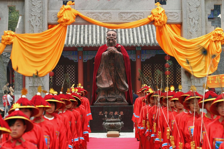 Mladi obučeni u tradicionalnu kinesku nošnju stoje ispred statue Konfučiju tokom obeležavanja godišnjice njegovog rođenja, Čangčun, 25. septembar 2005. (Foto: China Photos/Getty Images)
