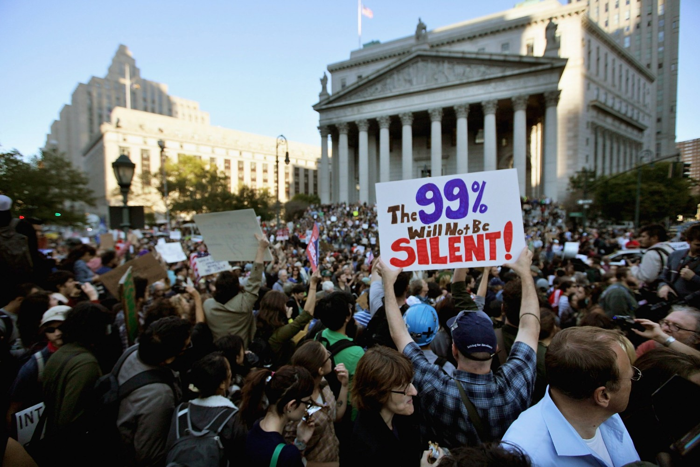 """Demonstranti sa transparentom na kome piše """"99 procenata neće biti tihi"""", tokom protesta u donjem Menhetnu, Njujork, 05. oktobar 2011. (Foto: Mario Tama/Getty Images)"""