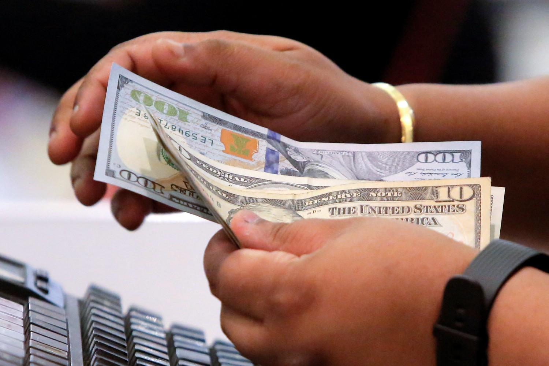 Radnik za kasom prima novac od potrošača u jednoj radnji na Menhetnu u Njujorku (Foto: Reuters/Andrew Kelly)