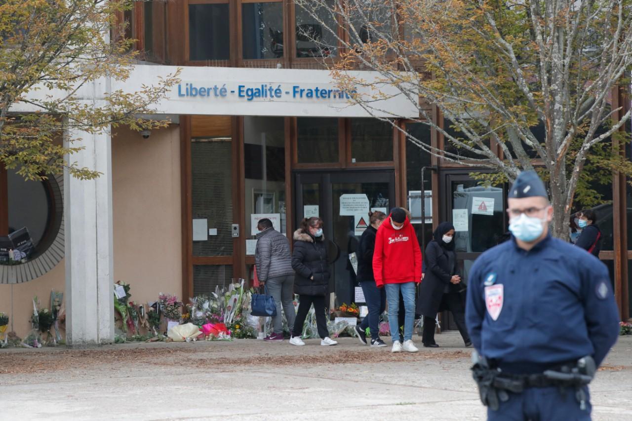 Pripadnik policije obezbeđuje školu u kojoj je radio ubijeni profesor dok učenici i građani polažu cveće, 17. oktobar 2020. (Foto: AP Photo/Michel Euler)