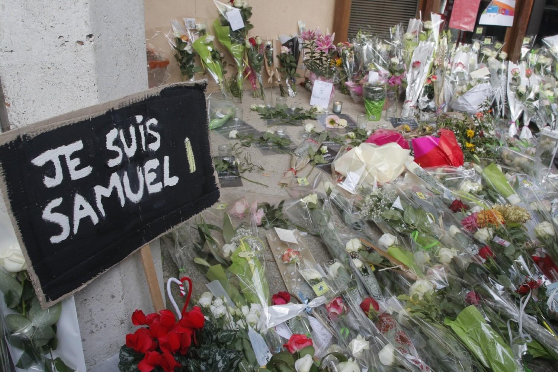 """Plakat sa natpisom """"Ja sam Samuel"""" na francuskom i položeno cveće ispred škole u predgrađu Pariza u kojoj je predavao obezglavljeni profesor istorije Samuel Pati, 17. oktobar 2020. (Foto: AP Photo/Michel Euler)"""
