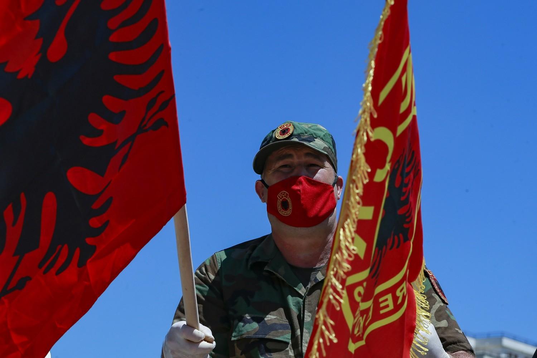 Ratni veteran OVK sa zastavama Albanije i OVK tokom protesta u Prištini, 09. jul 2020. (Foto: AP Photo/Visar Kryeziu)