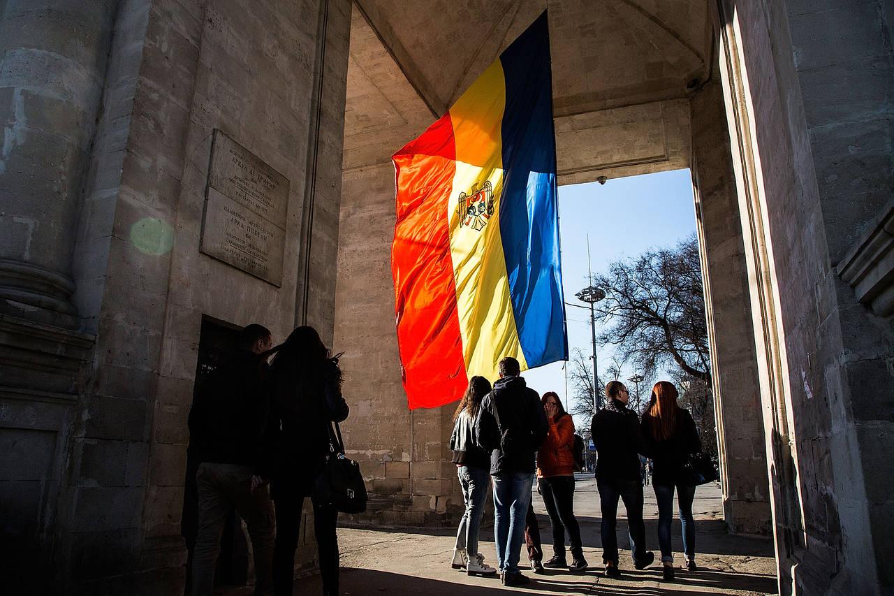 Građani Kišinjeva prolaze pored zastave Moldavije okačene unutar Trijumfalne kapije u centru grada, 08. mart 2015. (Foto: Carsten Koall/Getty Images)