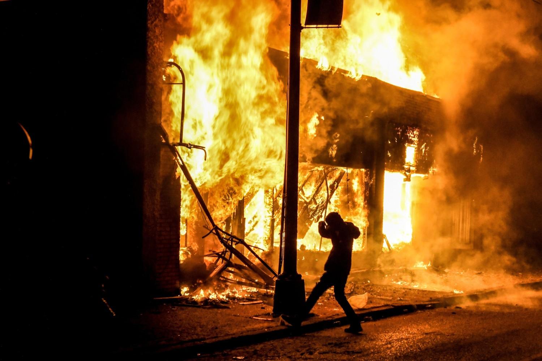 Demonstrant u blizini zapaljenih objekata tokom demonstracija zbog ubistva Džordža Flojda, Mineapolis, 29. maj 2020. (Foto: Chandan Khanna/AFP Photo)
