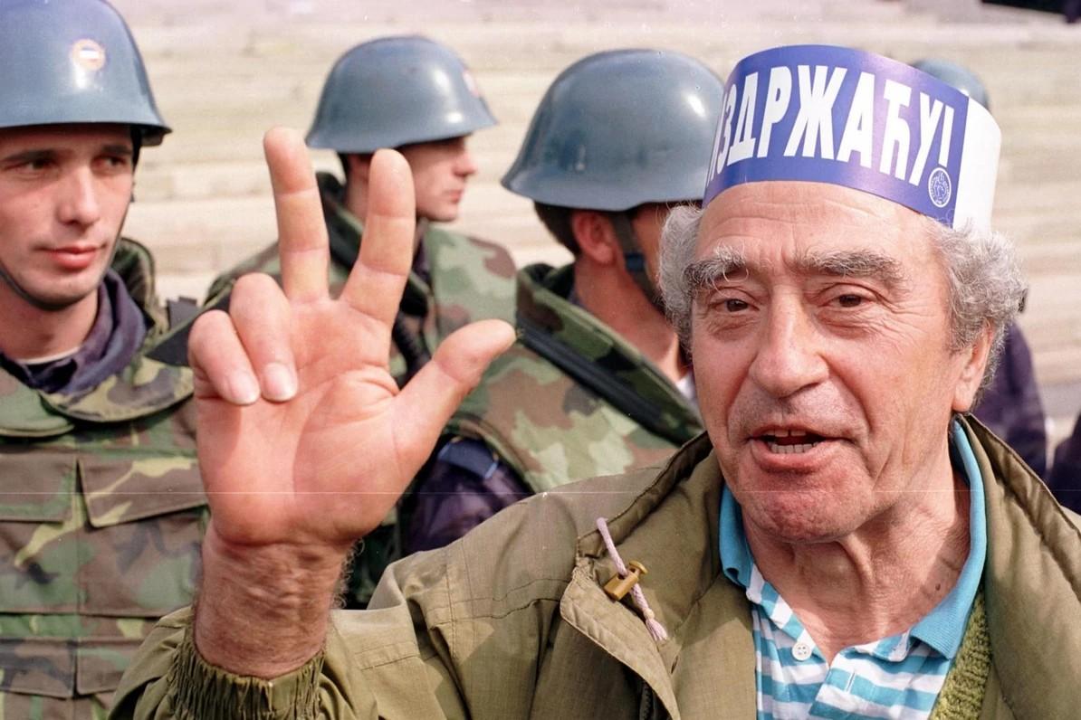 Stariji demonstrant sa podignuta tri prsta ispred kordona policije na ulazu u Dom Narodne skupštine tokom demonstracije 5. oktobra 2000. (Foto: Tanjug/Vladimir Dimitrijević)