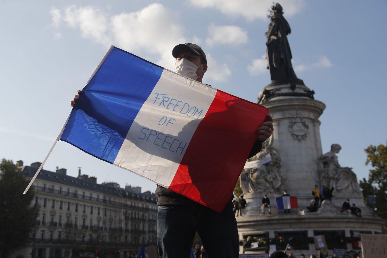"""Demonstrant sa francuskom zastavom na kojoj je ispisano """"Sloboda govora"""" tokom protesta zbog ubistva profesora u predgrađu Pariza, Pariz, 18. oktobar 2020. (Foto: AP Photo/Michel Euler)"""
