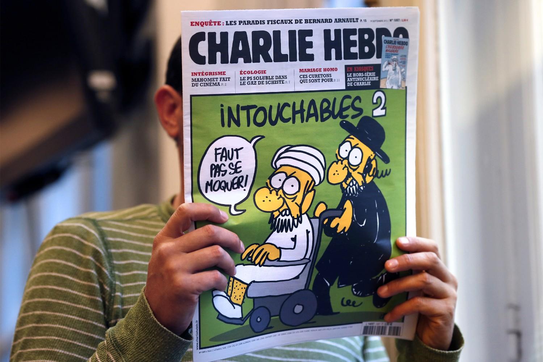 """Čovek čita zadnju stranicu francuskog satiričnog magazina """"Šarli ebdo"""" koji često sadrži provokativne karikature proroka Muhameda (Foto: Thomas Coex/AFP/Getty Images)"""