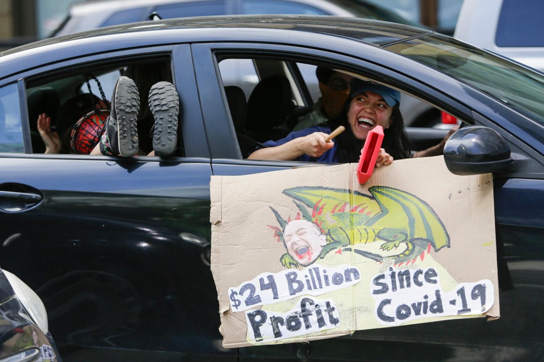 Демонстранти са транспарентом упереним против оснивача Амазона Џефа Безоса током аутомобилског каравана испред седишта Амазона у Сијетлу, 01. мај 2020. (Фото: Jason Redmond/AFP/Getty Images)