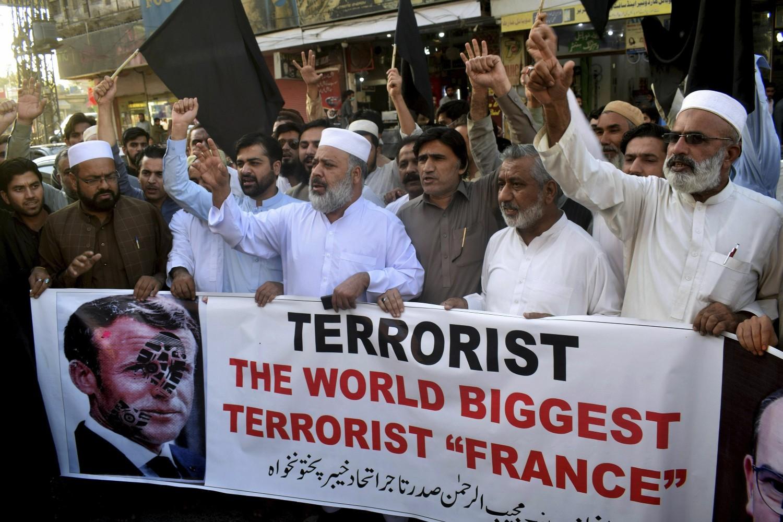 Pakistanski trgovci drže transparent sa unakaženom slikom francuskog predsednika Emanuela Makron tokom protesta zbog objavljivanja karikatura proroka Muhameda u Francuskoj, Pešavar, Pakistan, 26. oktobar 2020. (Foto: AP Photo/Muhammad Sajjad)