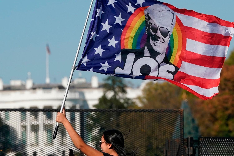 Pristalica Demokratske stranke i Džoa Bajdena maše zastavom dizajniranom u obliku LGBT boja i zastave SAD sa Bajdenovim likom ispred Bele kuće, Vašington, 07. novembar 2020. (Foto: Alex Edelman/AFP via Getty Images)