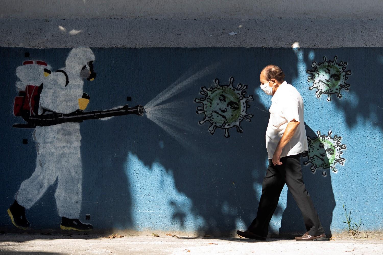 Čovek prolazi pored murala na zidu u Rio de Žaneiru koji oslikava borbu protiv koronavirusa (Foto: Silvia Izquierdo/AP Photo)