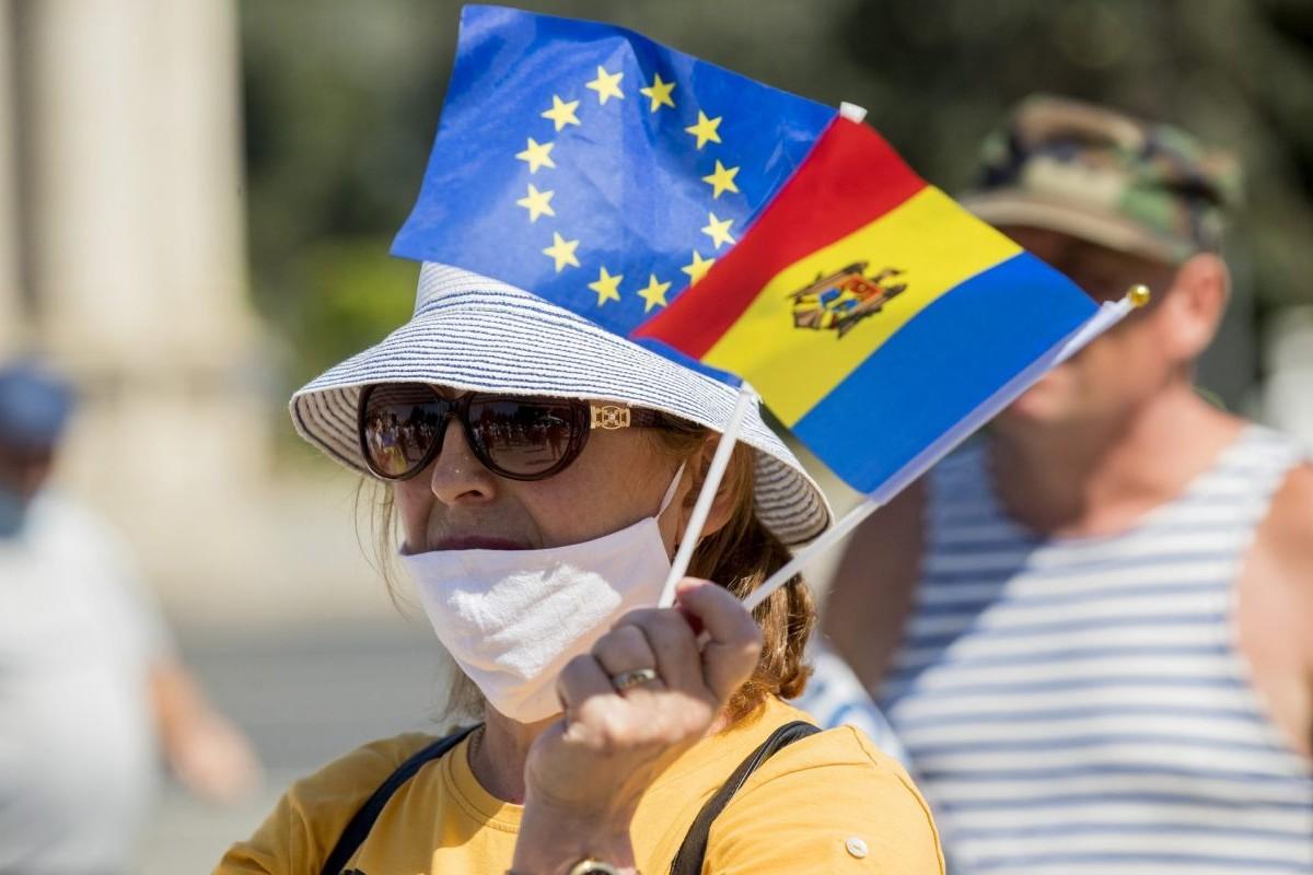 Žena drži zastavice Moldavije i Evropske unije tokom jednog protesta u Kišinjevu, avgust 2020. (Foto: EPA-EFE/Dumitru Dumitru)