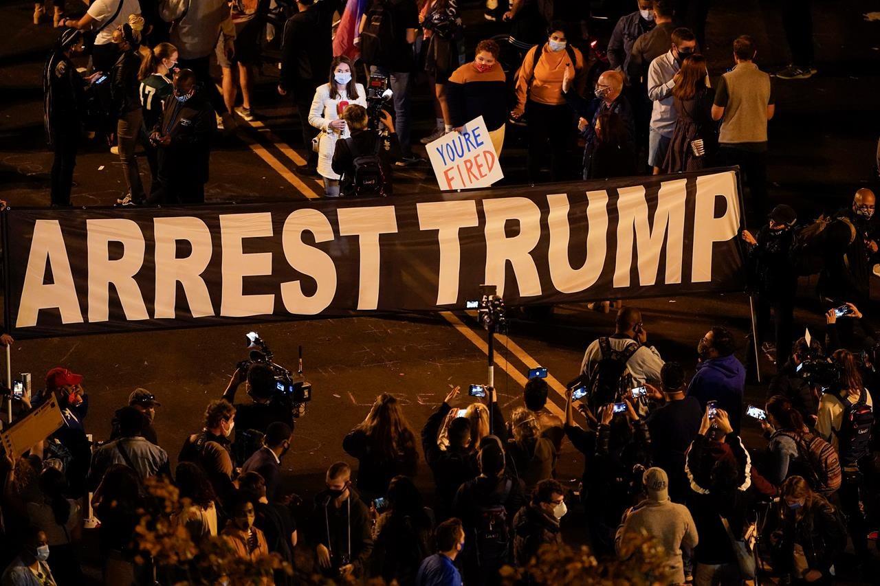 """Pristalice Džoa Bajdena tokom slavlja zbog njegove pobede na predsedničkim izborima sa transparentom na kome piše """"Uhapsite Trampa"""", Vašington, 07. novembar 2020. (Foto: AP Photo/Susan Walsh)"""