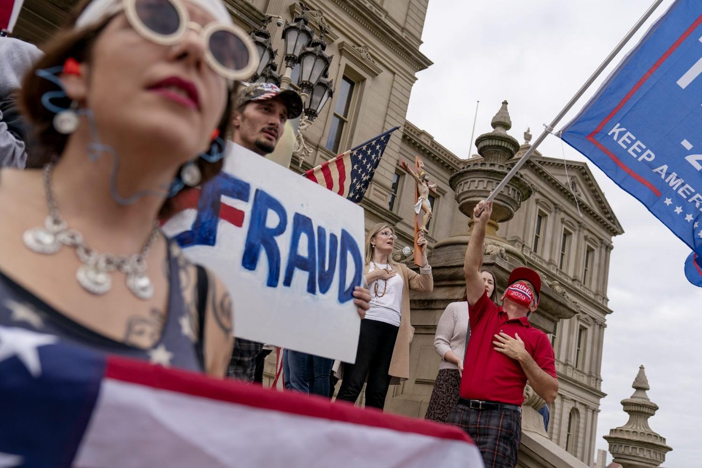 "Trampove pristalice sa zastavama i transparentom na kome piše ""Prevara"" tokom protesta zbog rezultata predsedničkih izbora ispred Kapitola u Lensingu, Mičigen, 08. novembar 2020. (Foto: AP Photo/David Goldman)"