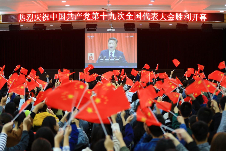 Studenti mašu kineskim zastavama dok slušaju prenos govora kineskog predsednika Si Đinpinga, 18. oktobar 2017. (Foto: Chinatopix via AP)