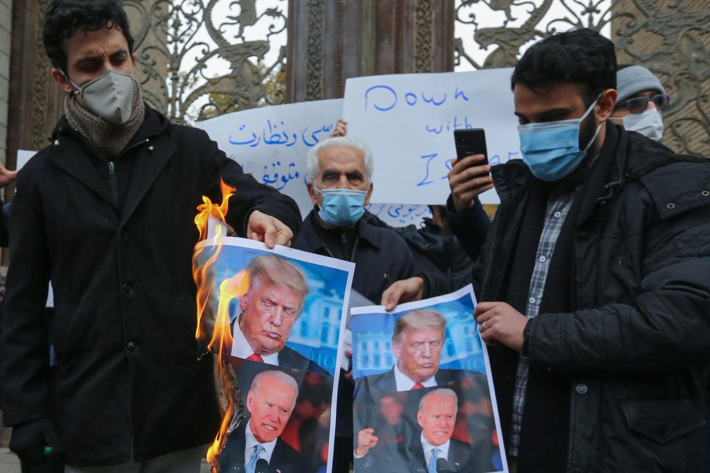 Iranski demonstranti sa zapaljenim plakatima na kojima su prikazani Donald Tramp i Džo Bajden u znak protesta zbog ubistva vodećeg iranskog nuklearnog naučnika Mohsena Fahrizadeha, 28. novembar 2020. (Foto: Atta Kenare/AFP Photo
