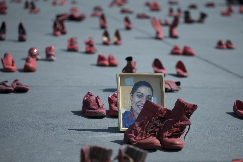 Portret ubijene žene smešten usred ženskih crvenih cipela koje su aktivisti postavili u znak protesta protiv nasilja nad ženama na glavnom trgu Meksiko Sitija, 11. januar 2020. (Foto: AP Photo/Christian Palma)