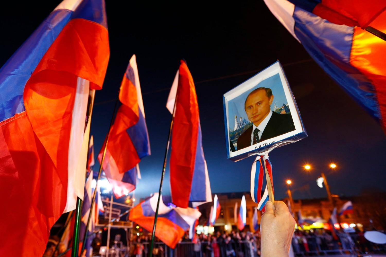 Građani Simferopolja sa ruskim zastavama i slikom ruskog predsednika Vladimira Putina tokom slavlja na glavnom gradskom trgu, 21. mart 2014. (Foto: Reuters/Shamil Zhumatov)