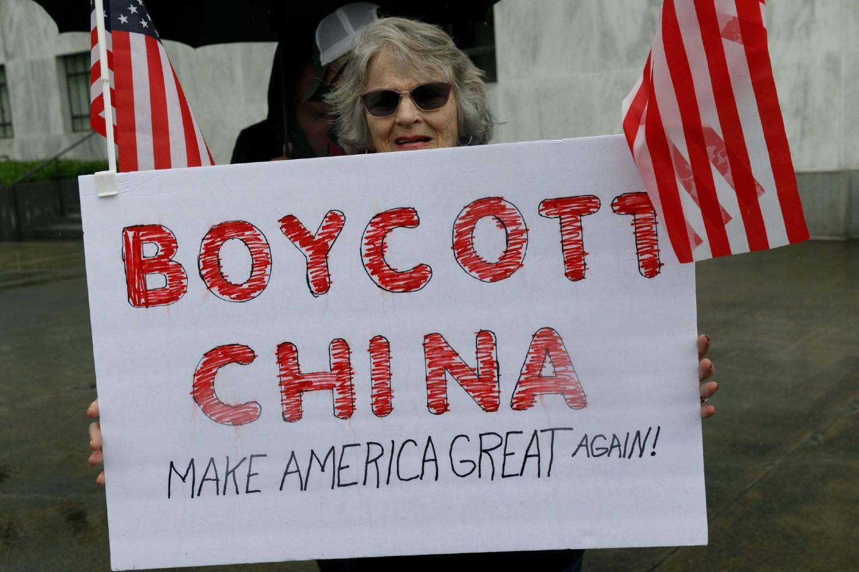 """Žena demonstrant sa transparentom na kome piše """"Bojkotuj Kinu"""" tokom protesta ispred Kapitola u Salemu (Oregon) zbog zatvaranja usled pandemije koronavirusa, 02. maj 2020. (Foto: John Rudoff/Anadolu Agency via Getty Images)"""