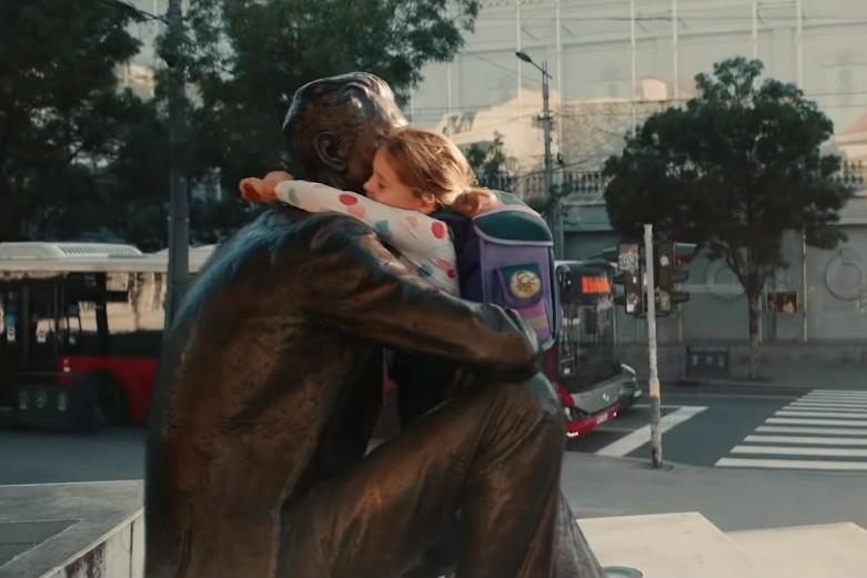 """Scena u kojoj devojčica grli statuu Borislava Pekića na Cvetnom trgu u Beogradu u sklopu reklame """"Vi ste svet"""" (Foto: Snimak ekrana/Vi ste svet)"""