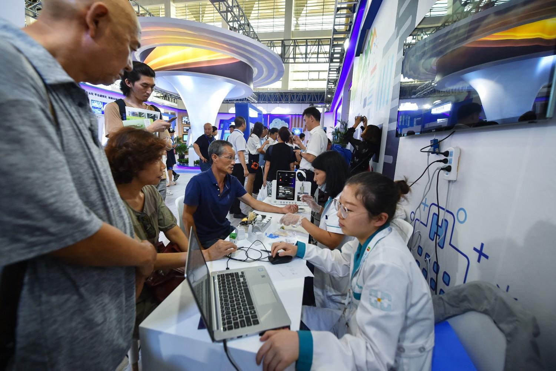 """Posetioci isprobavaju servis zdravtsvene usluge baziran na internetu tokom izložbe """"Internet plus zdravstvena zaštita"""" na sajmu u Jinčuanu, 06. septembar 2019. (Foto: Xinhua/Li Mangmang)"""