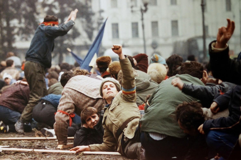 Demonstranti gestikuliraju rukom ležeći na zemlji tokom borbi između Čaušeskuovih snaga i antirežimskih pristalica, Bukurešt, 24. decembar 1989. (Foto: Reuters/Fatih Saribas)